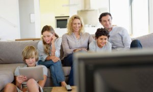 family in front of TV with ipad and screens